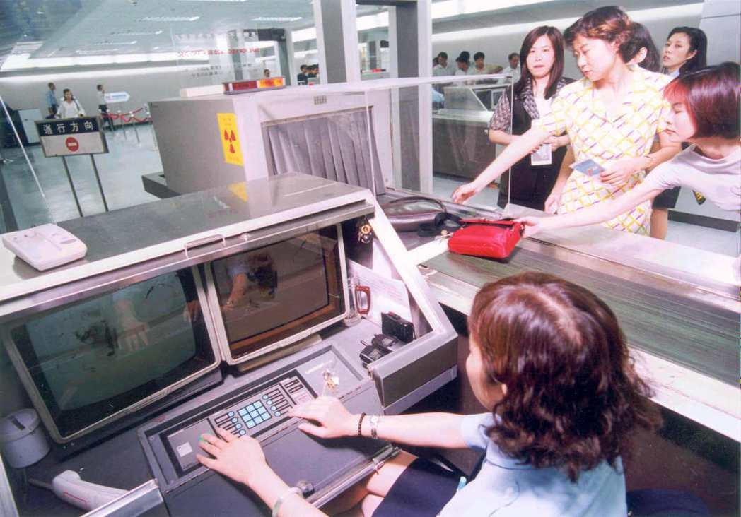 機場安檢人員操作X光儀器檢測旅客行李。 報系資料照