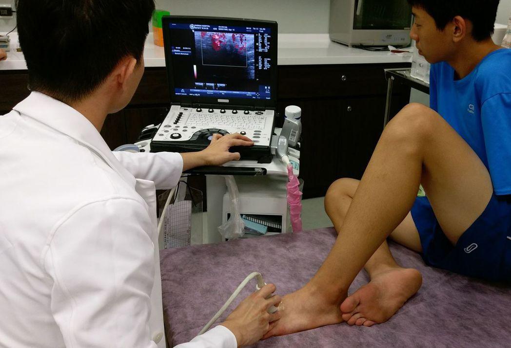 謝姓學生(右)回診時,醫師王偉全(左)檢視謝姓學生第2趾蹠骨恢復情況。圖/長安醫...