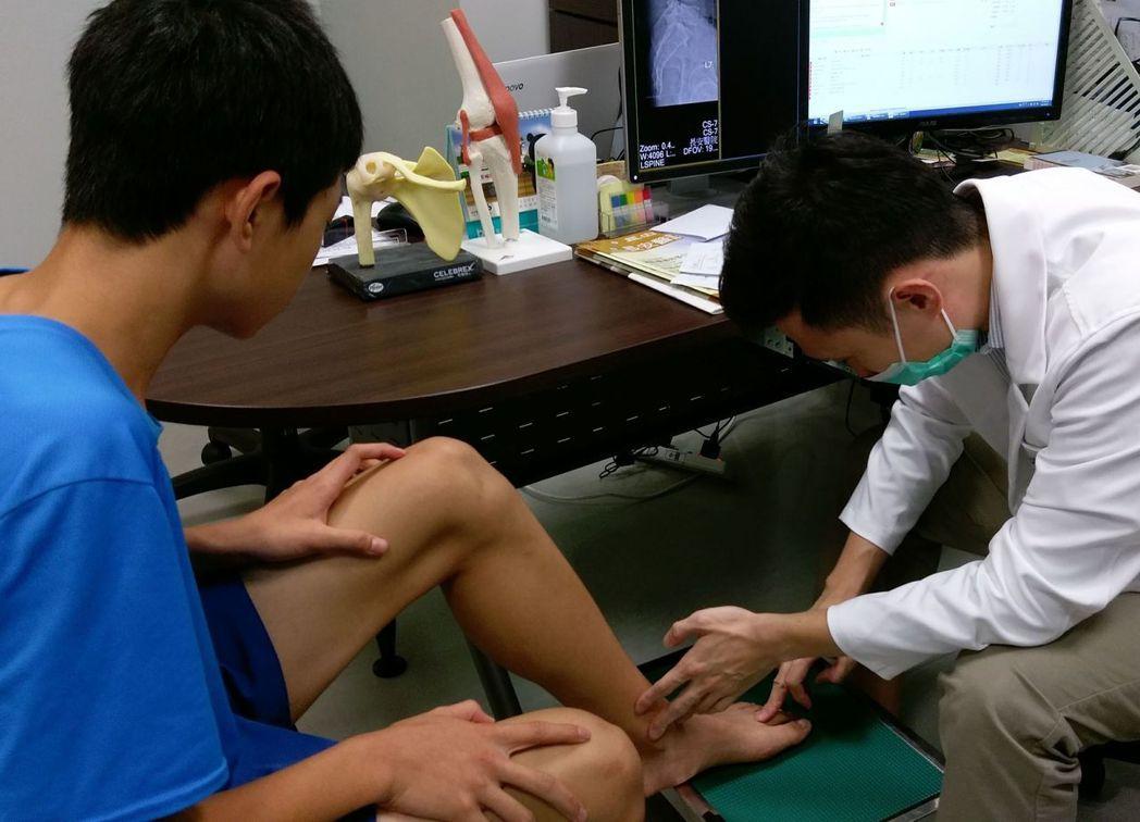 謝姓學生(左)回診時,醫師王偉全(右)檢視謝姓學生第2趾蹠骨恢復情況。圖/長安醫...