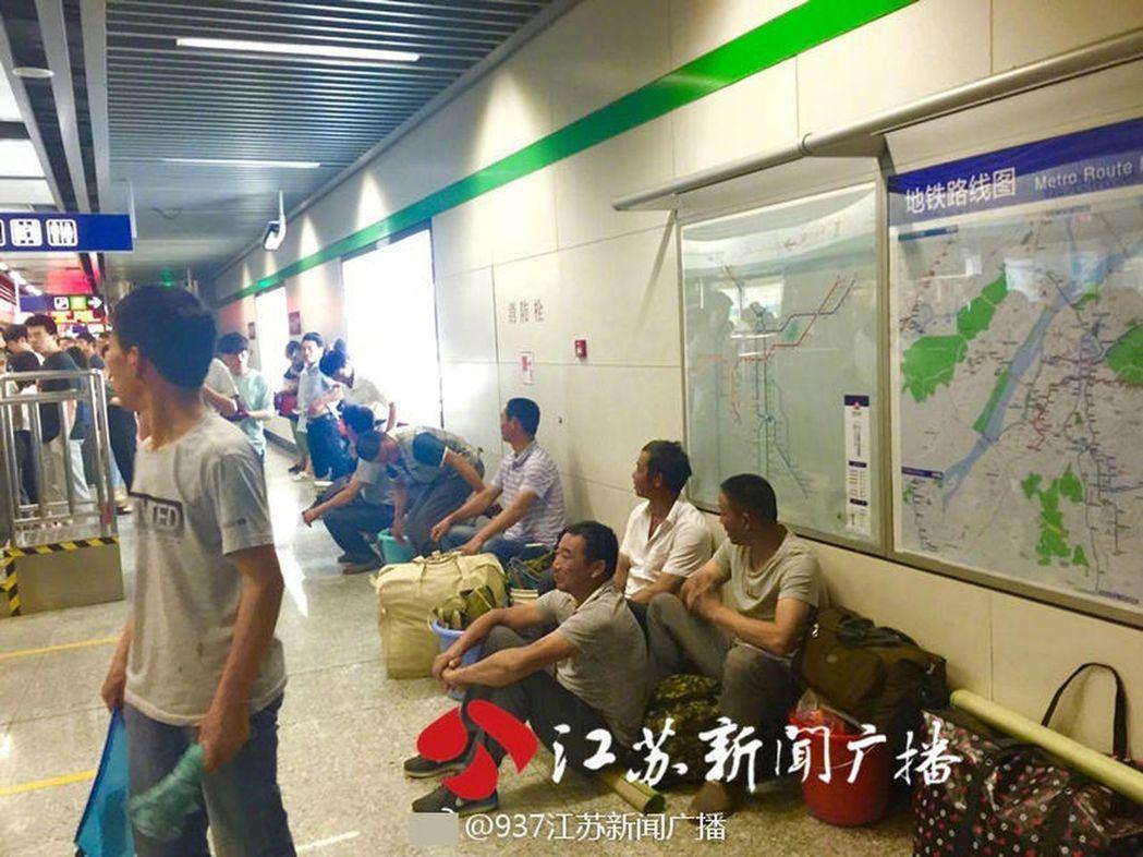 南京地鐵一群農民工怕耽誤上班族出行,在地鐵站坐等兩個多小時。(取材自江蘇新聞廣播...