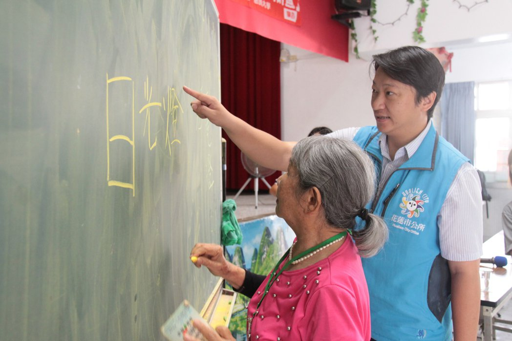85歲的洪粘甜一時忘了日光燈的「燈」字,市長魏嘉賢在旁耐心提點。 圖/慈濟大學提...