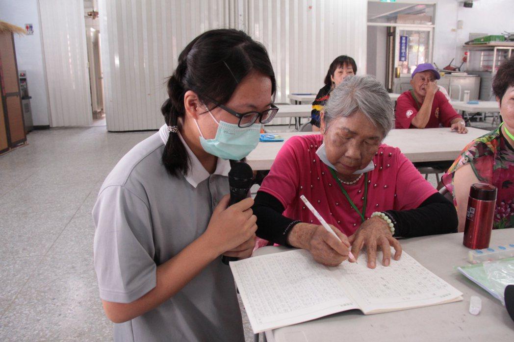 慈濟大學護理系學生教導老人家識字。圖/慈濟大學提供