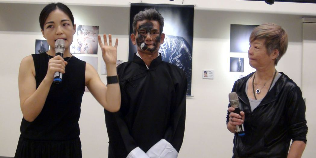 「破繭癒火重生」定義美麗攝影展的策展人陳美麗(右)和彩繪師馬家駒(左)透過顏損彩...