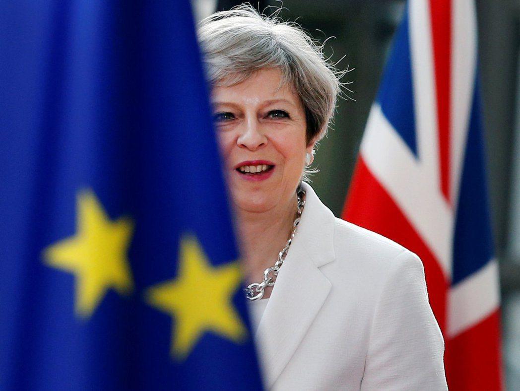 英國首相梅伊23日參加歐盟峰會,恰好位在歐盟與英國國旗之間。(路透)
