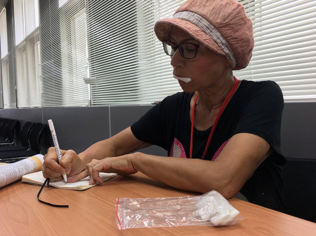 漸凍症病友寶姐無法說話,受訪時咬著自製棉花口水棒,一邊傾聽記者的問題,一邊拿著筆...
