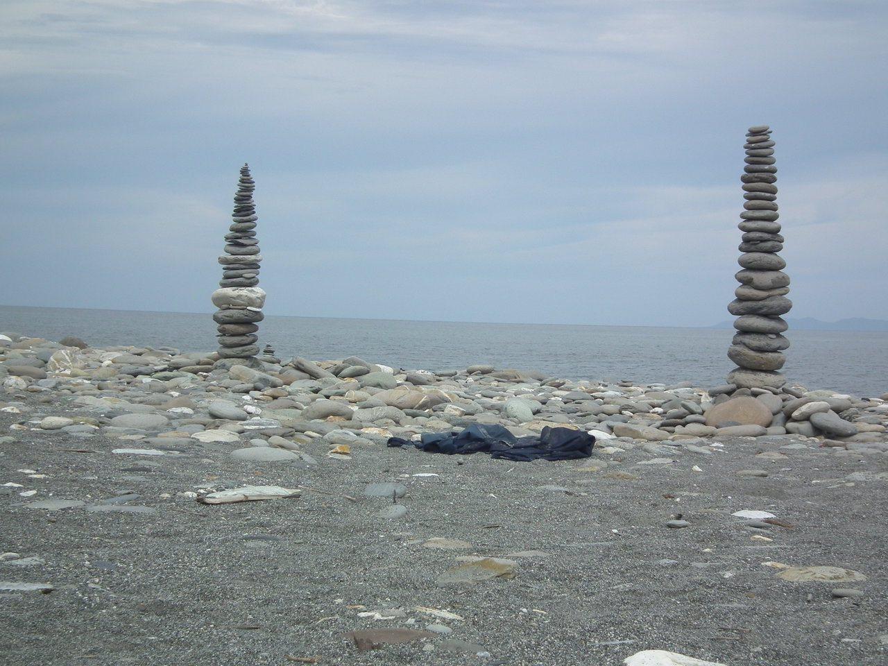 台東市「國際地標」海灘近日出現神祕石堆陣,石頭堆疊規模大小不一,聳立在海灘上,吸...