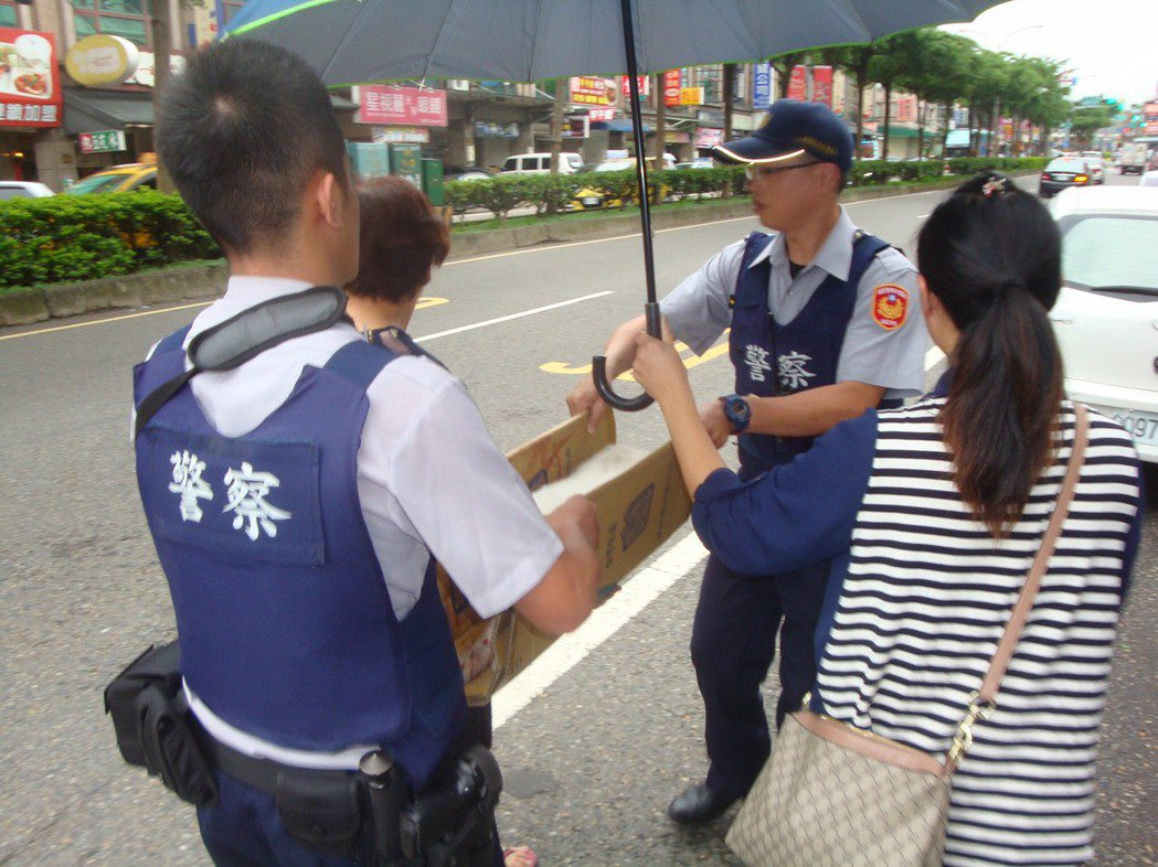 警員用紙箱製作擔架婦人熱心撐傘。圖/桃園市平鎮警分局提供