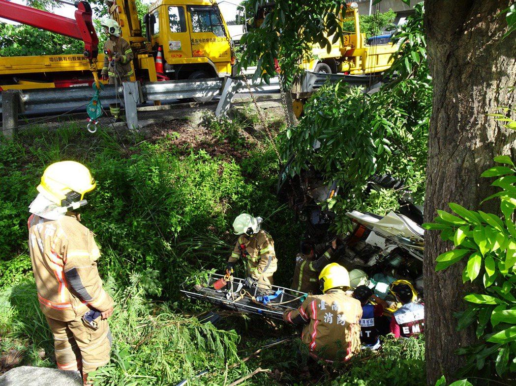 國8台南新市段下午發生大貨車失控翻落邊坡,台南市消防隊員協力將司機救出。記者謝進...