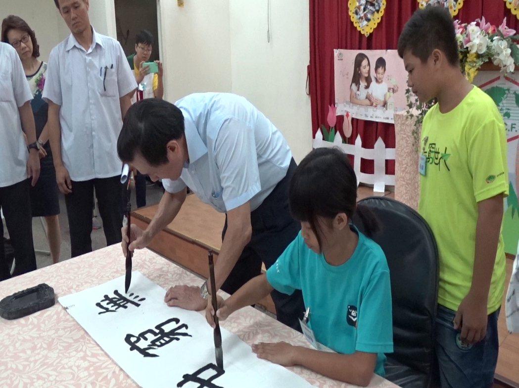 前總統馬英九(右3)今天下午到彰化家扶二林服務處,與小朋友一起寫書法。記者何炯榮...