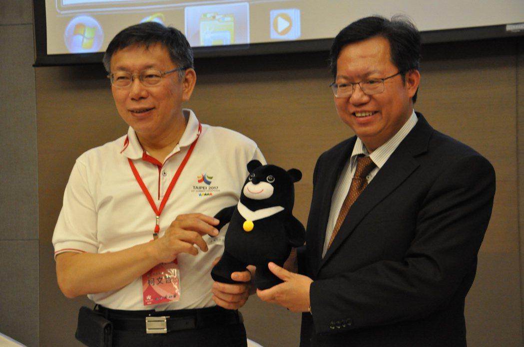 台北市長柯文哲(左)率市府團隊與桃園市長鄭文燦(右)的市府團隊交流並互贈禮物。記...