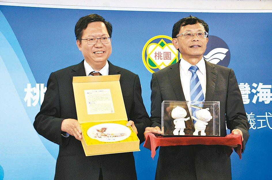 桃園市長鄭文燦(左)與國立台灣海洋大學校長張清風,昨簽合作意向書後互贈禮物。 記...