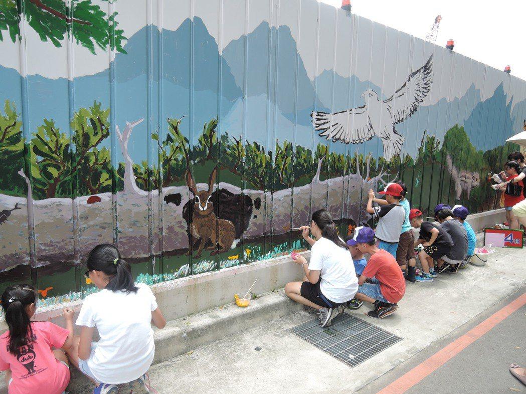 新北市板橋中山國小師生昨天一起為學校改建工程的施工圍籬彩繪,讓枯燥圍籬變得多彩多...