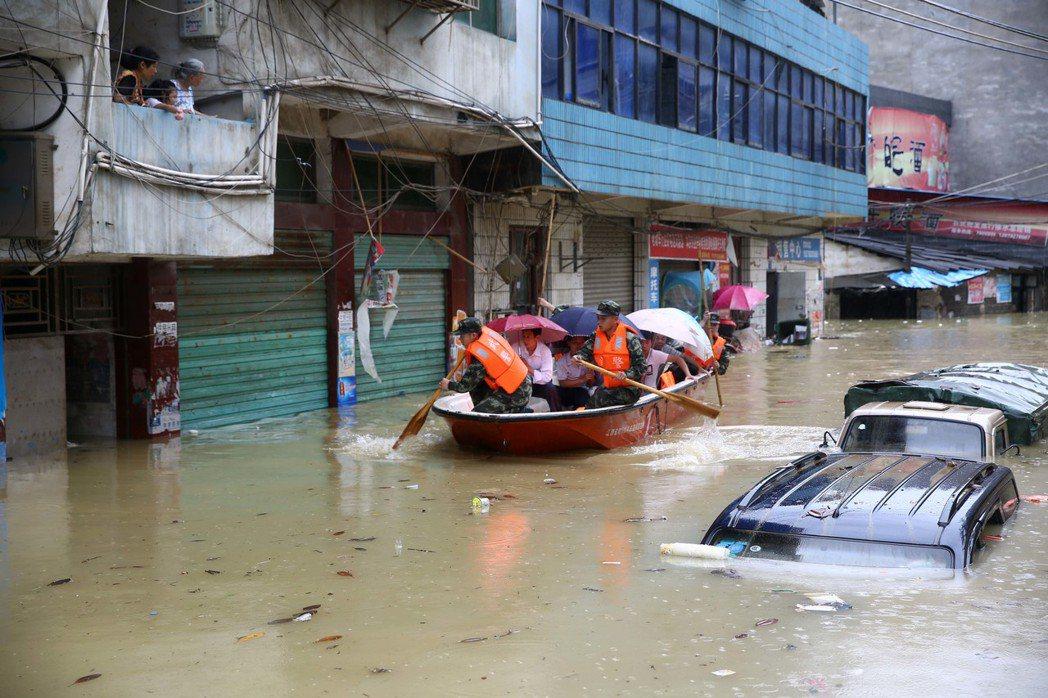 武警官兵24日在九江市修水縣寧州鎮蘆塘村轉移被洪水圍困群眾。(新華社)