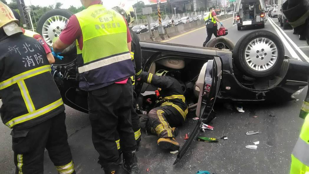 消防人員爬進車內助他脫困。記者江孟謙/翻攝