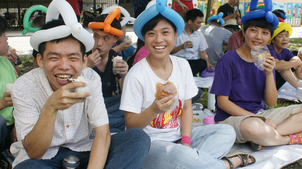 二林社區大學師生今天到喜樂保育院萬合院區,在草坪上陪伴憨兒享受快樂的星期天。記者...