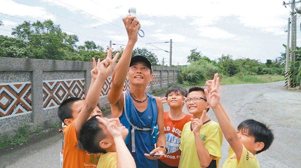 林明哲用Samsung Gear 360全景相機與花蓮崇德國小學童開心合照。 圖...