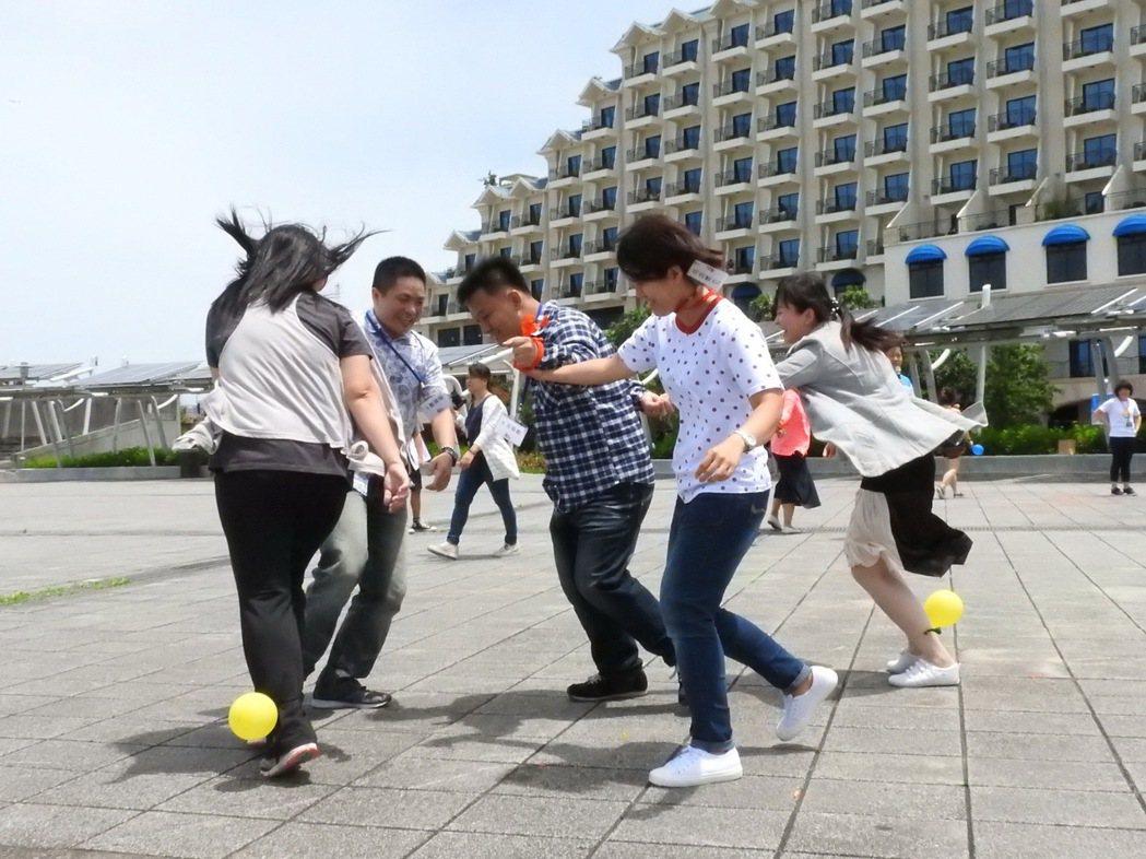 新北市民政局昨天在淡水漁人碼頭福容飯店舉行未婚聯誼,參加的未婚男女大玩踩氣球等團...