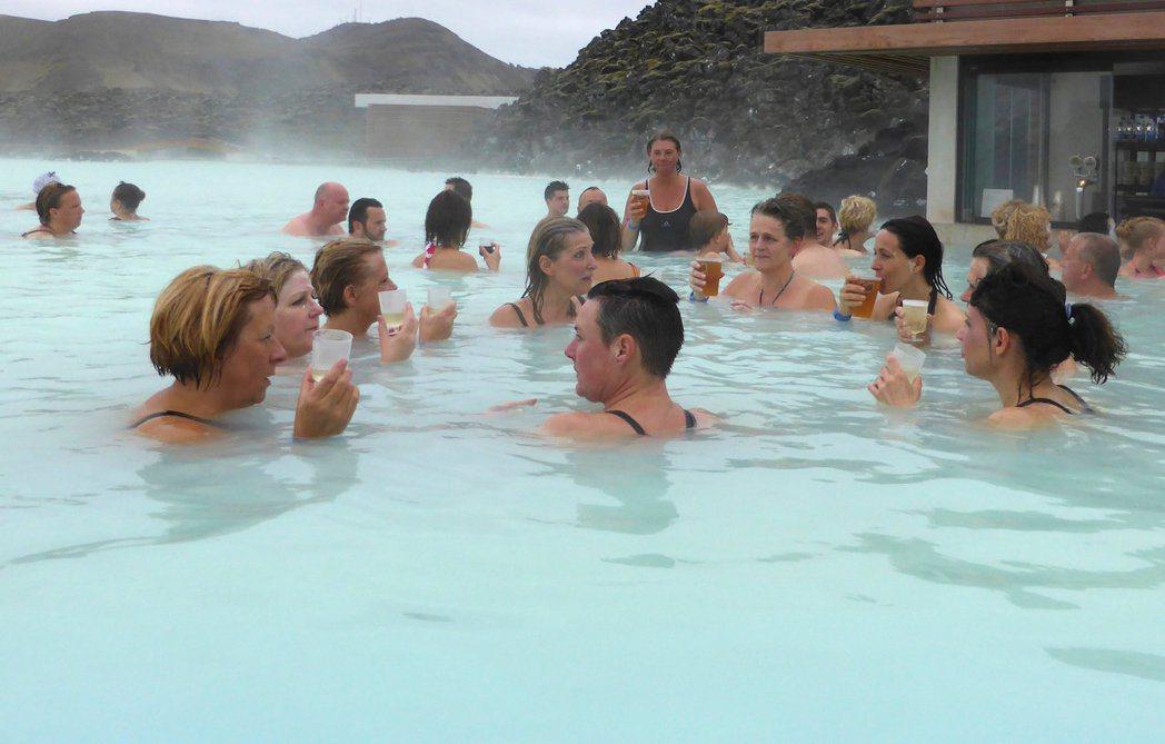 電影取景地點讓冰島旅遊業者大賺觀光財,圖為遊客在格林達維克地熱池泡溫泉。 路透資...