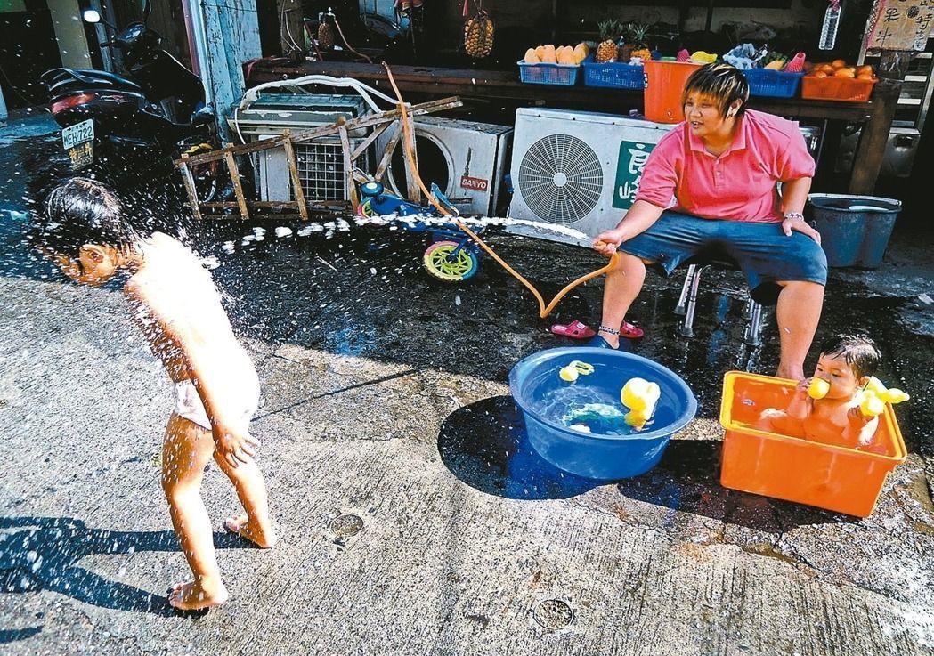 台東民眾昨灑水為小朋友消暑。 記者潘俊偉/攝影