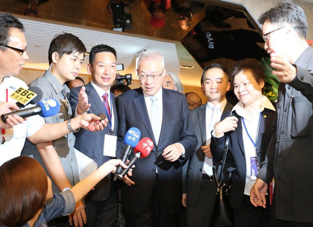 前副總統吳敦義(中)出席畫展開幕儀式,致詞後他步出會場,面對媒體提問一例一休,他...