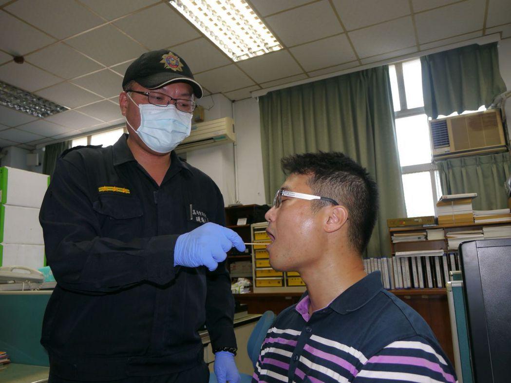 警方鑑識人員示範口腔唾液檢體取樣,過程不到5分鐘。記者徐白櫻/攝影