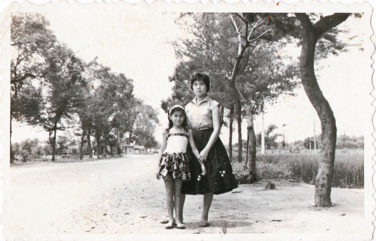 廖玉蕙(左)和三姊攝於前門縱貫公路旁,夏日,兩旁的鳳凰花紅似火。右後方是分岔的兩...