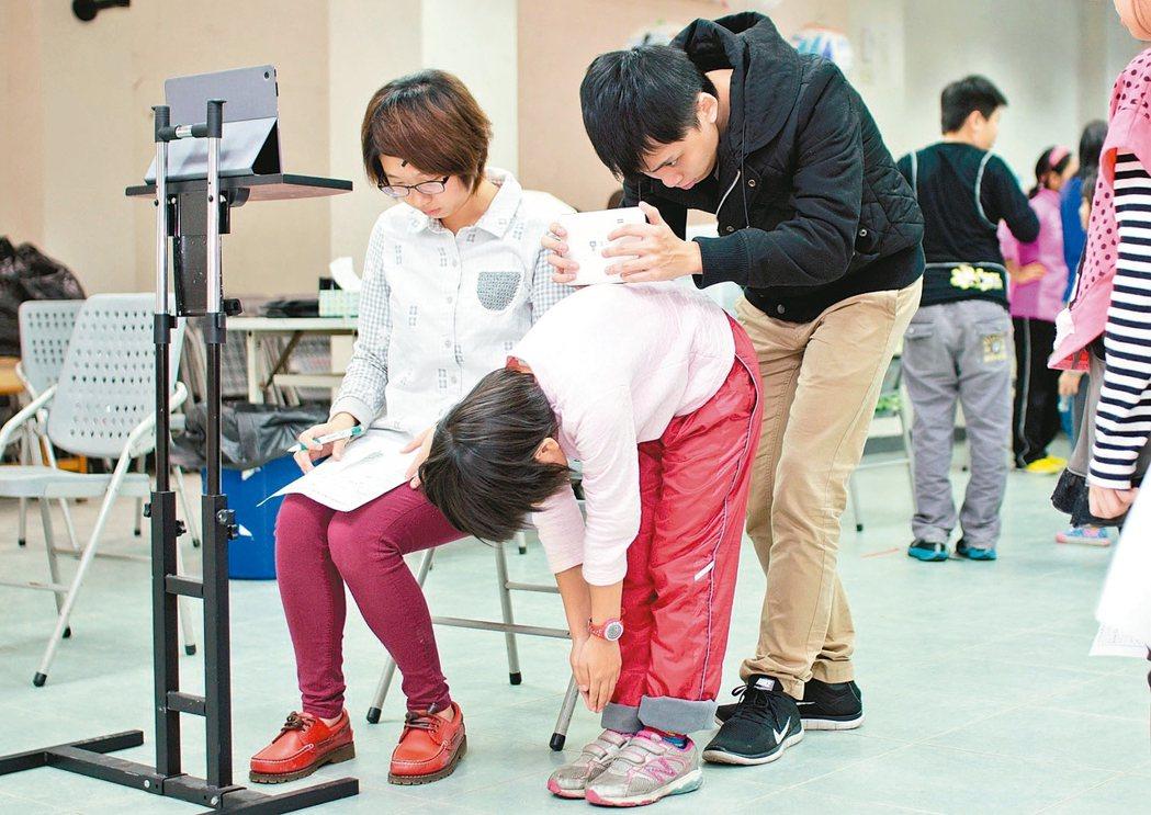 牛爸爸健康促進關懷協會成員,利用儀器測量學童脊柱側彎情形。 記者卜敏正/翻攝