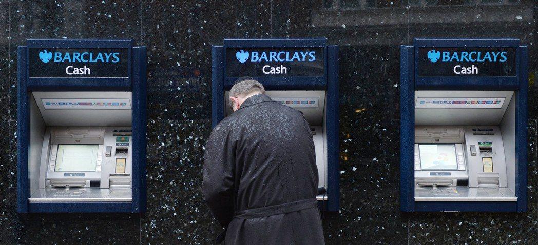 全英國仍有94%的成人使用自動提款機,圖為一位英國民眾在巴克萊銀行提款機前領錢。...