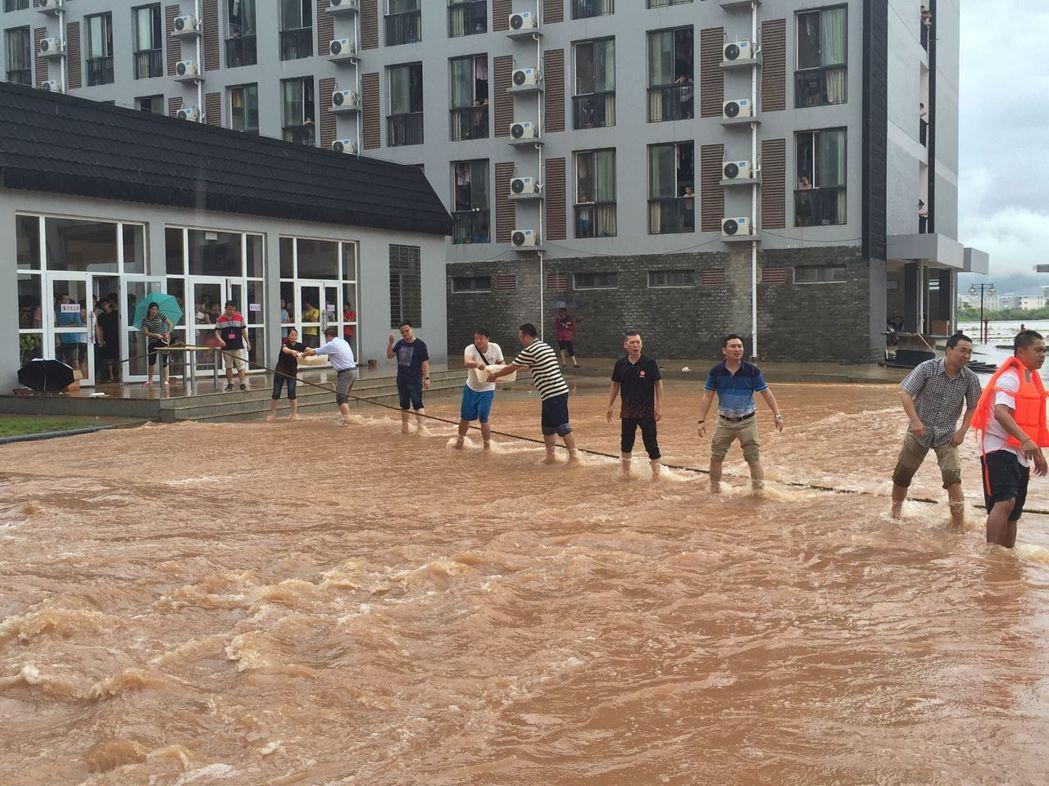 廣西桂林市26日遭遇強降雨,桂林電子科技大學花江校區內,學校教職工及後勤人員拉起...
