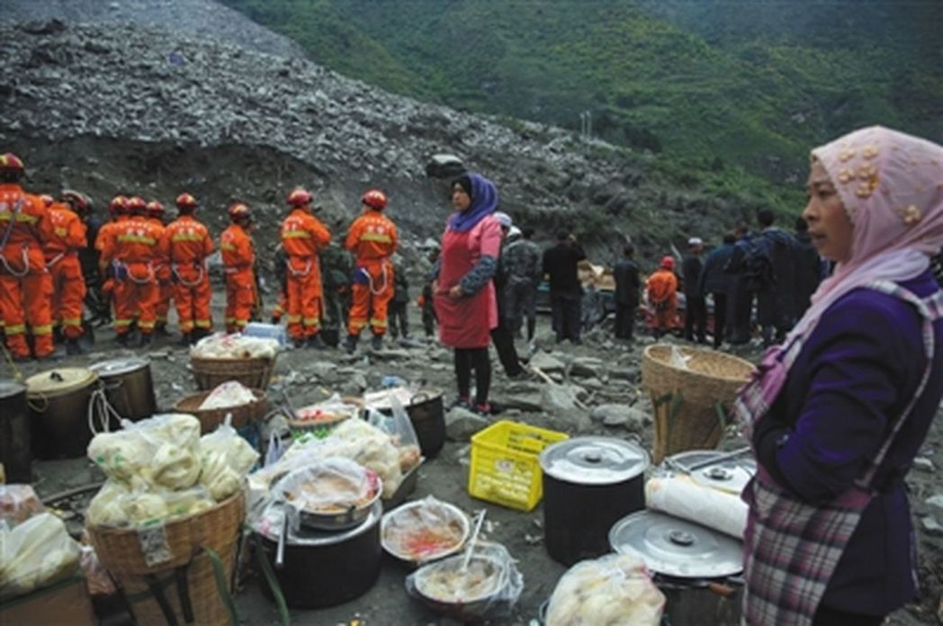 新磨村附近村子的村民25日自發做好了饅頭、熟食送到垮塌現場,提供給救援人員。(取...