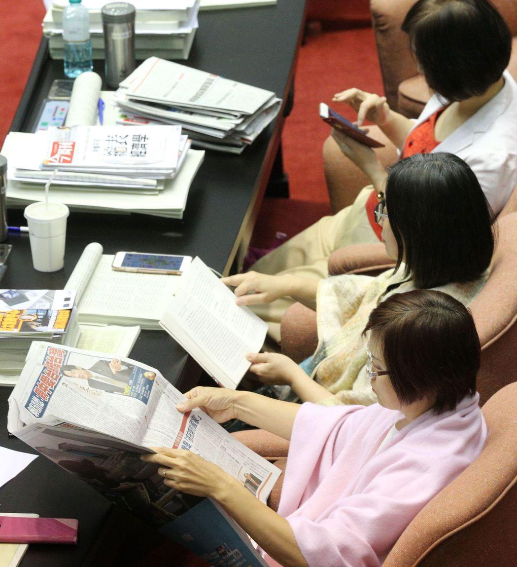 委員看報紙、滑手機,消磨時間。 記者陳正興/攝影