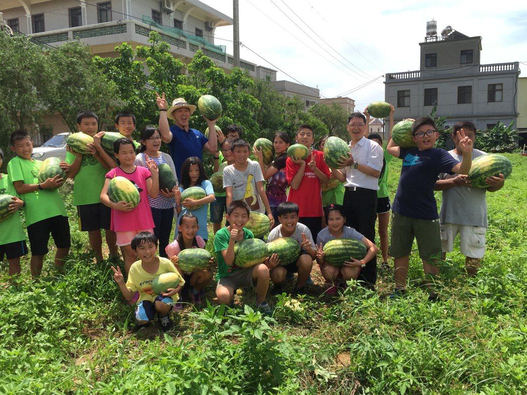 金門多年國小的小朋友昨天採收自己種植的西瓜,校長陳來添(後排右三)與小朋友開心的...