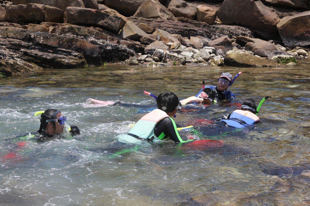福連國小畢業典禮的重頭戲,就是帶著裝著九孔幼貝的袋子泳渡貢寮卯澳灣。圖/新北市農...