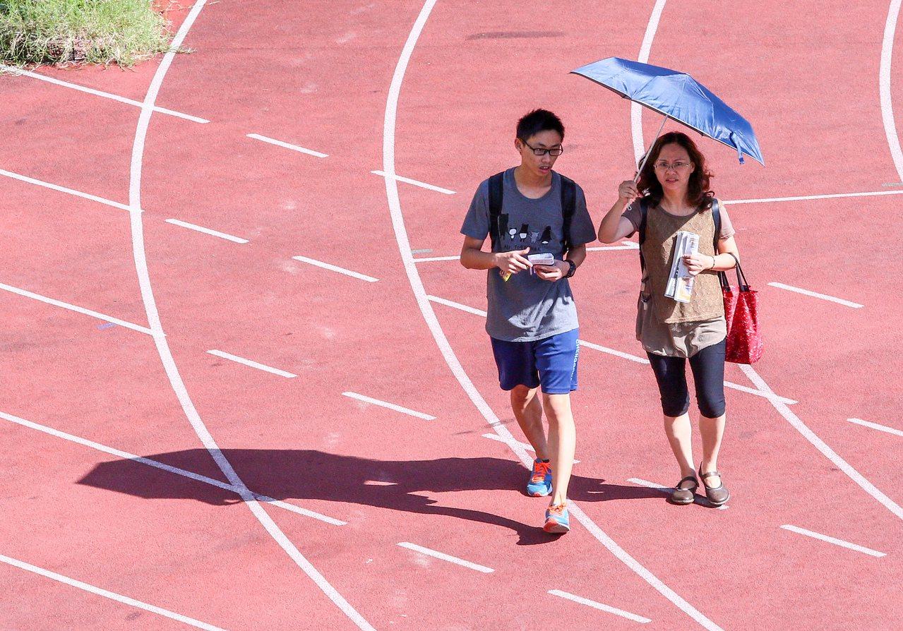 大學指考考生在媽媽的洋傘遮陽下進入考場。本報資料照/記者趙文彬攝影
