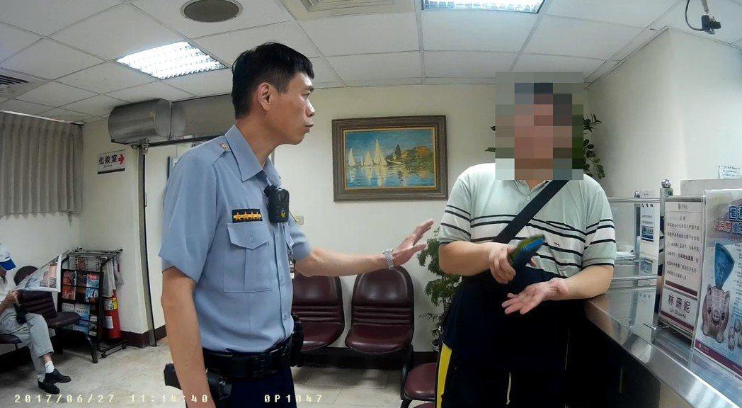 劉姓男子在銀行被警方勸阻。圖/記者廖炳棋翻攝