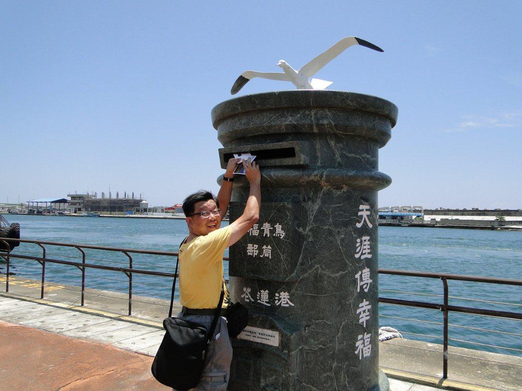 香港遊客在花蓮港1號碼頭親子遊憩區內的蛇紋石幸福青鳥郵筒,郵寄風景明信片給親友。...