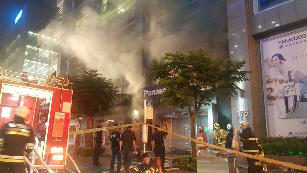 台北市某商辦大樓火警,現場冒出大量濃煙,影響人車通行。記者李奕昕/攝影