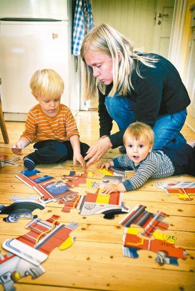 一名瑞典年輕媽媽陪伴兩位稚子玩拼圖。 法新社