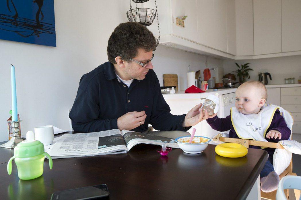 挪威父親塔洛斯請育嬰家在家帶小孩,他試著讓寶貝女兒用奶瓶喝水。 路透