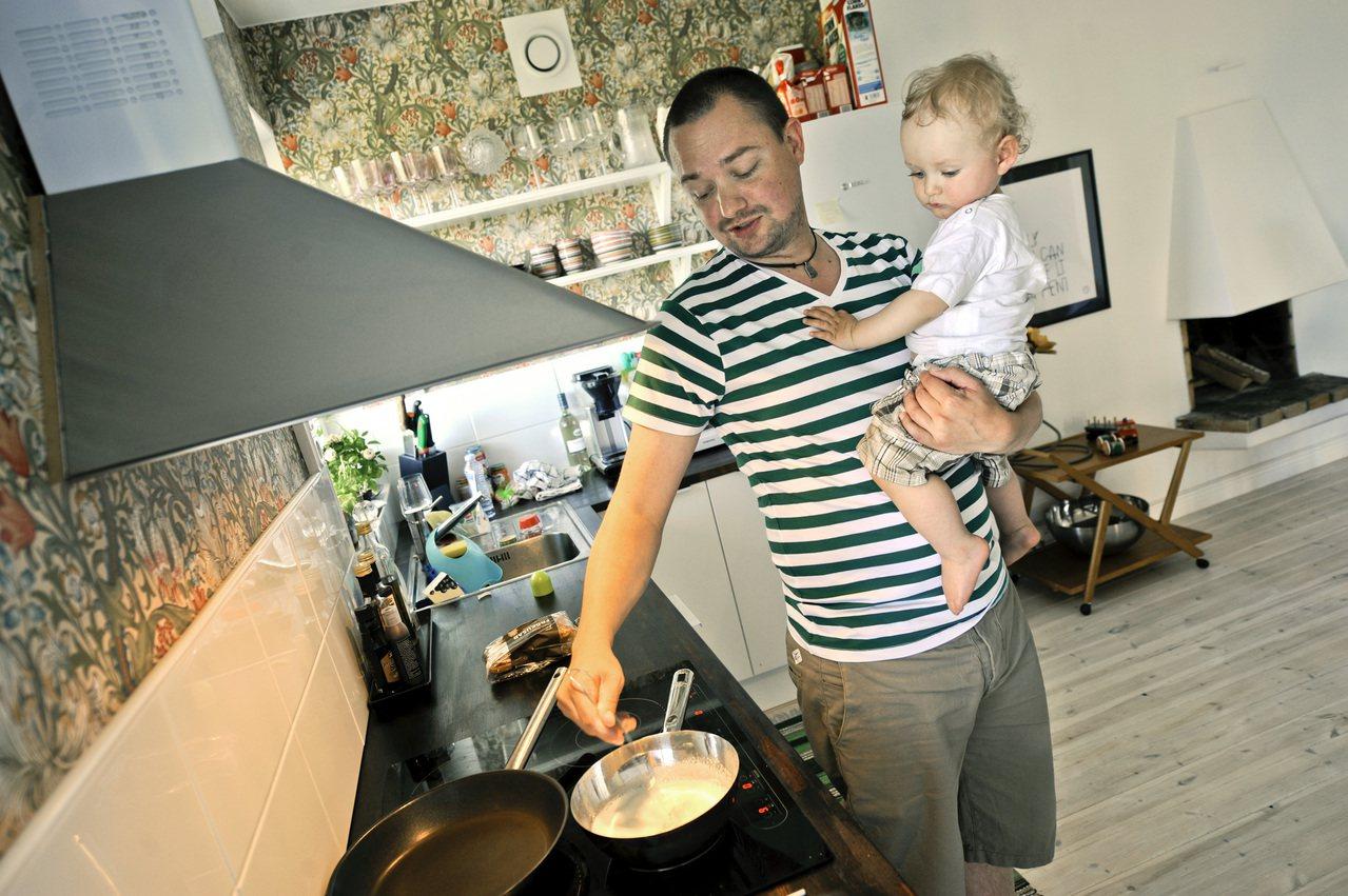 瑞典父親霍格森一手抱著幼子,一手調理食物。 美聯社