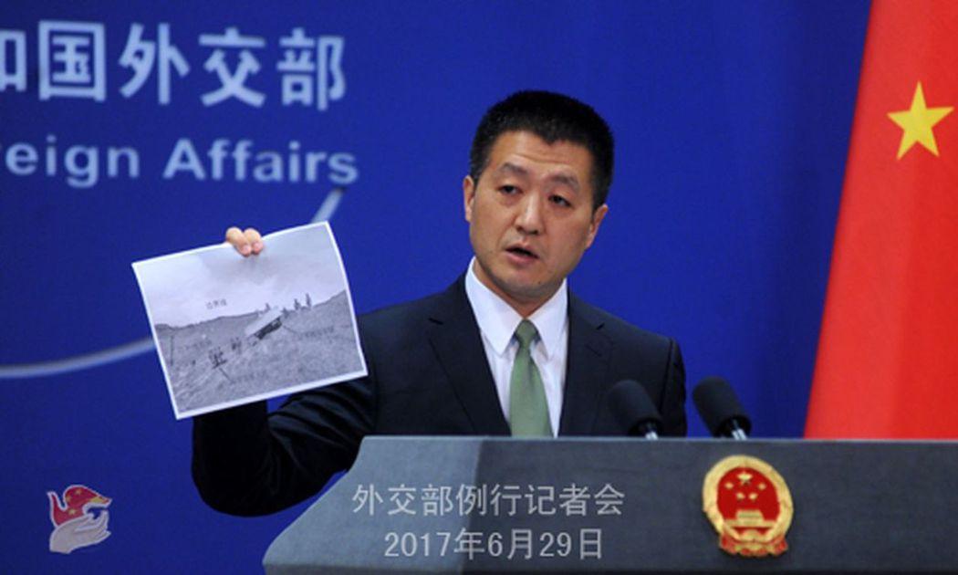 中國外交部發言人陸慷在記者會者手舉照片。(取材自中國外交部官網) 蘇妍鳳