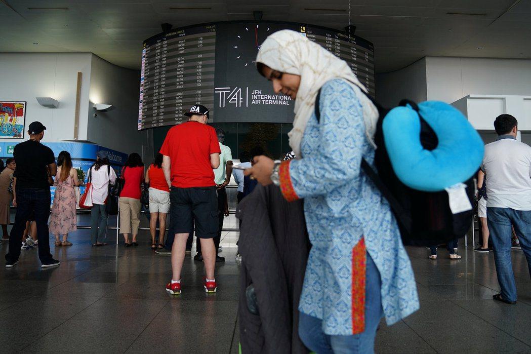 川普總統修訂的旅遊禁令29日晚生效,圖為穆斯林女旅客從紐約甘迺迪機場入境美國。(...