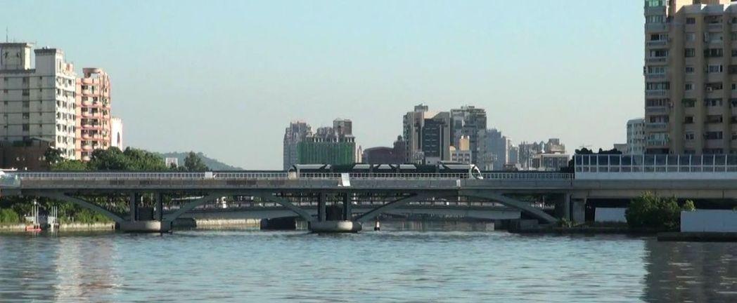 高雄輕軌列車穿越愛河入海口上方的橋面。記者楊濡嘉/攝影