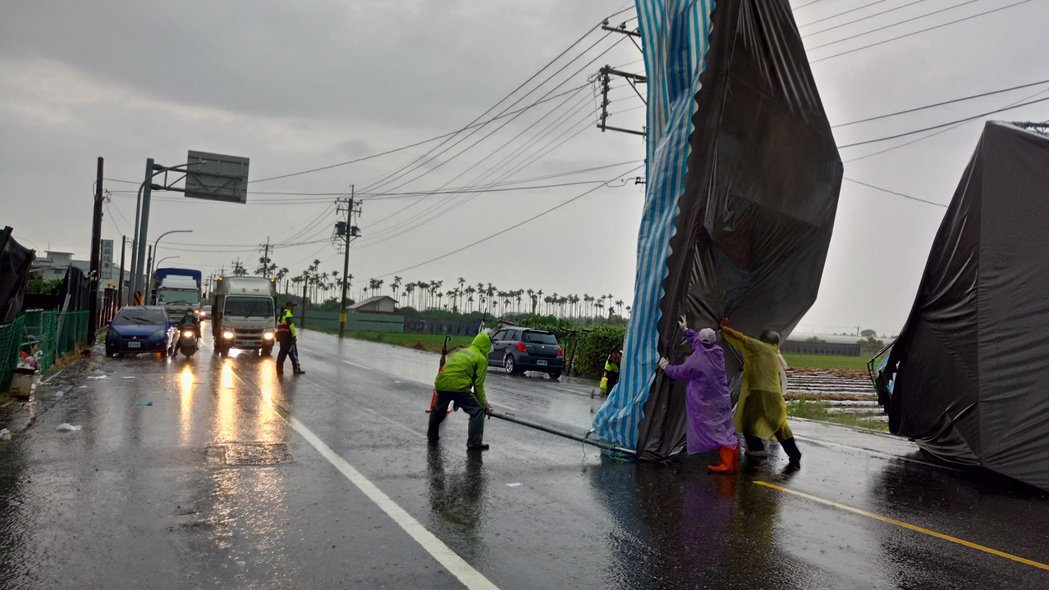 狂風暴雨吹來帆布屋頂,擋住了民雄安和路。記者卜敏正/攝影