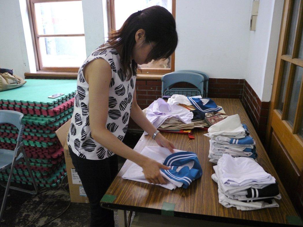 教務主任吳彗瑜整理即將空運出國的學生制服,以後非洲學童將會穿這些「旗山國小」制服...