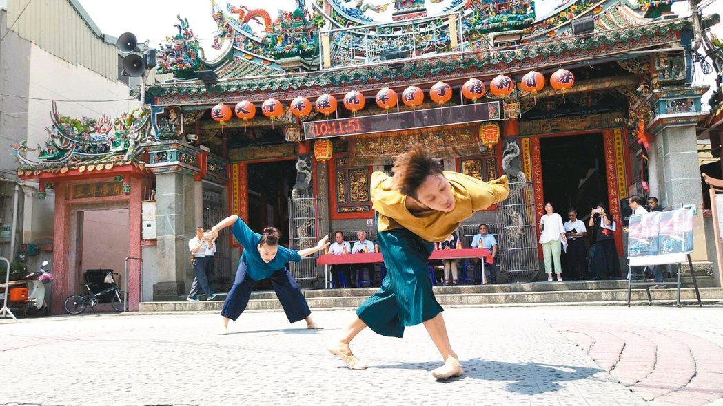 年輕舞者李泰棋(右)、王玟甯,昨天在嘉義縣民雄鄉大士爺廟前示範演出,幻化多變的舞...