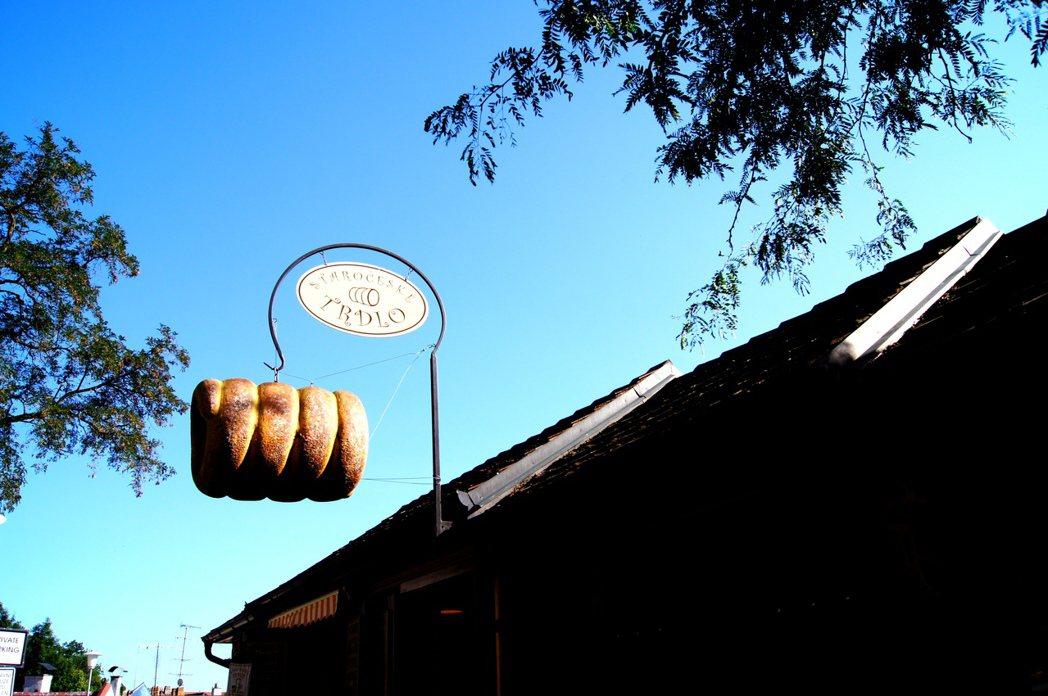 捷克琥珀卡白色城堡附近,有家賣麵包的咖啡館,招牌上吊著一個超大麵包捲。 記者張錦...