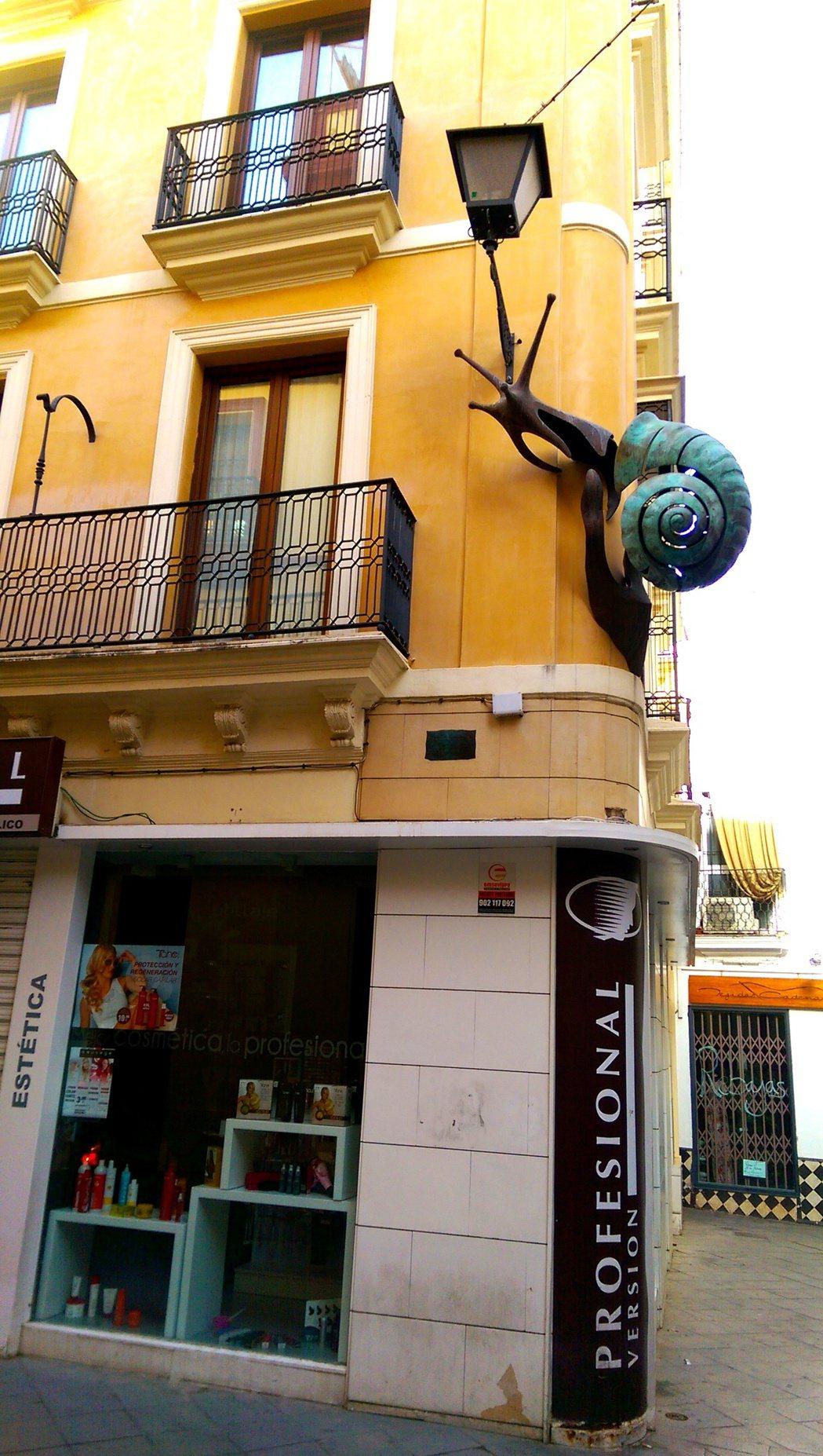 西班牙有家化妝品店,遠遠看二樓外牆爬著一隻大蝸牛,近看是燈的造型。 記者張錦弘/...