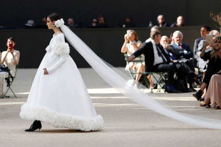 壓軸的白色婚紗禮服以大朵山茶花刺繡於裙襬與兩側臂膀,曳地頭紗更增添浪漫情懷。圖/...