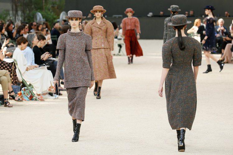香奈兒將艾菲爾鐵塔搬進巴黎大皇宮裡,搭配模特兒腳踩的黃沙地,讓造訪來賓就像環坐在...